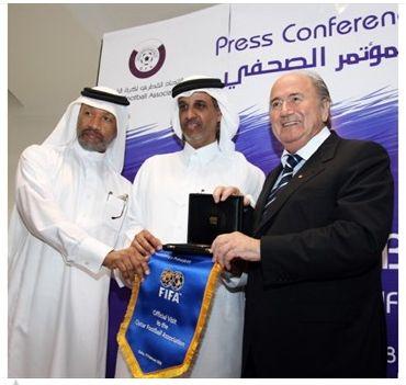 MBH, Scheich Salman und Sepp Sonnenkönig halten gemeinsam einen FIFA-Wimpel